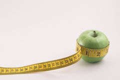 Apple and Tailor's Tape. A Granny Smith Apple and a Tailor's Measuring Tape Royalty Free Stock Images