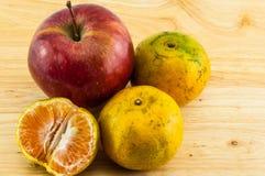 Apple & tangerine στο ξύλινο υπόβαθρο Στοκ Εικόνες