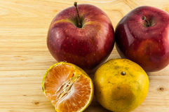 Apple & tangerine on wood background Stock Photography