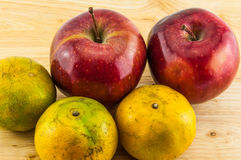 Apple & tangerine on wood background Stock Image