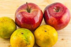 Apple & tangerine on wood background Royalty Free Stock Image