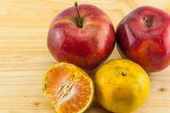 Apple & tangerine on wood background Royalty Free Stock Photo