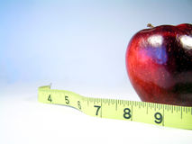Apple and tape measure. Apple on white with measuring tape signifying weight watching or weight loss royalty free stock photo