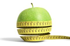 Apple with tape measure. Green apple with tape measure in a white  background Royalty Free Stock Photo