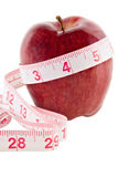 Apple and Tape Measure. Red delicious apple with a tape measure wrapped around it. Isolated white background Royalty Free Stock Photo