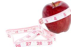 Apple and Tape Measure. Red delicious apple surrounded by a tape measure on an isolated background. Good health concept Stock Image