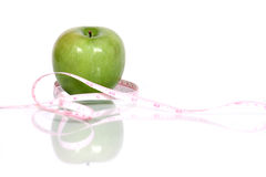 Apple and tape measure. Measuring tape wrapped around green apple, isolated on white background Royalty Free Stock Photos