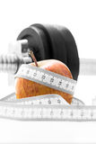 Apple with a tape measure and gym weight. Fresh apple wrapped in a tape measure with a gym weight in the background in a weight loss, health, diet and fitness Stock Images