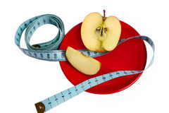 Apple with tape measure on the red plate. Isolated on white Royalty Free Stock Photography