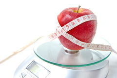 Apple and tape measure on a scale Royalty Free Stock Photo