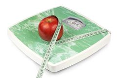 Apple and tape measure on a scale Stock Photography