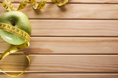 Apple and tape measure on wooden floor top view Royalty Free Stock Photo