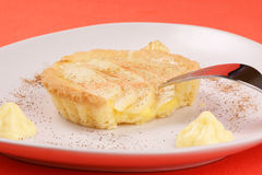 Apple tart. Small apple tart served on a white plate with custard and cinnamon Stock Image