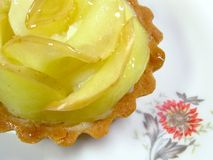 Apple tart. A tartelette aux pommes, or apple tart, on a floral white plate stock photo