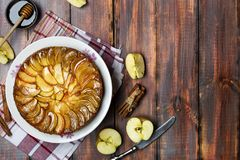 Apple tart with caramel and cinnamon on wooden table. Homemade apple tart with caramel and cinnamon on wooden table stock photography