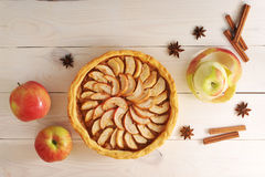 Apple tart with cinnamon and apples on a white wooden background. Top view Stock Photography