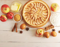 Apple tart, ingredients - apples and cinnamon. Apple tart, ingredients - apples, flour, butter and cinnamon on rustic wooden background - top view Stock Image