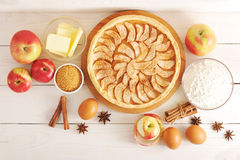 Apple tart, ingredients - apples and cinnamon. Apple tart, ingredients - apples, flour, butter and cinnamon on rustic wooden background - top view Stock Images