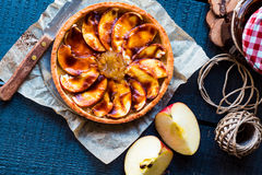 Apple tart with pear jam and caramel, top view. Round apple tart with pear jam and caramel on a dark background, top view royalty free stock photography