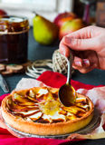 Apple tart with pear jam pour caramel, hands Stock Photo