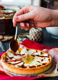 Apple tart with pear jam pour caramel, hands Stock Image
