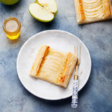 Apple tart, puff pastry strips with vanilla custard. On a stone background Stock Photo