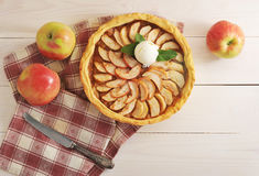 Apple tart with a scoop of ice cream. On a napkin on wooden white background - top view Stock Images