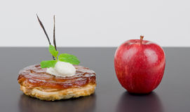 Apple tart Tatin with red apple. Upside down apple tart Tatin alongside red apple it was made from . French classic dessert , finished with Chantilly cream, mint Royalty Free Stock Images