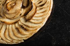 Apple tart. Traditional french sweet dessert on dark marble background. Delicious, appetizing, homemade pie with slices Royalty Free Stock Image