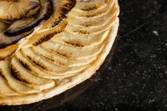 Apple tart. Traditional french sweet dessert on dark marble background. Delicious, appetizing, homemade pie with slices. Of fresh fruits. Copy space, closeup Stock Photo