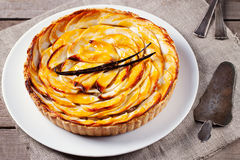 Apple tart with vanilla pod on a white plate Traditional holiday dessert Royalty Free Stock Photography