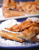 Apple tart with whipped cream and apricot glaze. Piece of an apple tart baked in puff pastry with an apricot glaze dusted in powdered sugar and served with fresh Royalty Free Stock Photo