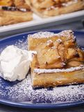 Apple tart with whipped cream and powdered sugar royalty free stock photography