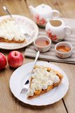 Apple tart with whipped cream, red apples and teaware. On wood table Royalty Free Stock Photo