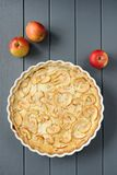 Apple tart with whole apples on grey stripped background Royalty Free Stock Photo