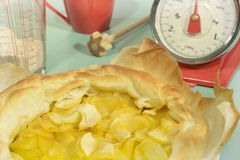 Apple tarte Kitchen scale Querl Grain retro look. An apple tarte on baking paper fresh out of the oven placed on a table. A kitchen scale, a mug, a querl and a Royalty Free Stock Photo