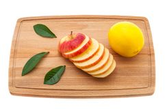 Apple tasty, fresh and juicy with green leaves and lemon on a cutting board made of wood. stock photography