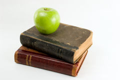 Apple for the teacher. Green apple on antique school book stack royalty free stock images