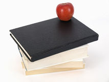 Apple for Teacher. A stack of books and a ripe red delicious apple over a white background Stock Photography