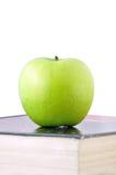 An apple on a textbook. Green apple on a textbook Stock Photos