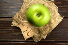 Apple with thank you lable on a piece of burlap over dark wooden background. Happy thanksgiving day concept. Top view