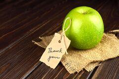 Apple with thank you lable on a piece of burlap over dark wooden background. Teacher`s day concept, copy space