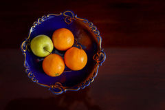 An apple and three oranges Stock Photo