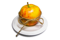 Apple tied with twine on a white plate (top front view) Stock Image