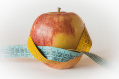 Apple tighten with a meter. A meter is tighten around a beautiful apple Royalty Free Stock Images