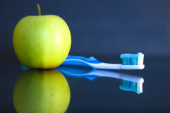 Apple and toothbrush. One green apple and toothbrush isolated on a blue  background Royalty Free Stock Photos