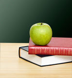 Apple on top of books Royalty Free Stock Photos