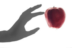 Apple Touched by a Shadow Hand Royalty Free Stock Photos