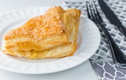 Apple turnover pastry on plate with utensils and cloth Royalty Free Stock Photo