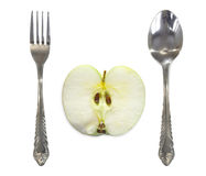 Apple tussen vork en lepel stock foto